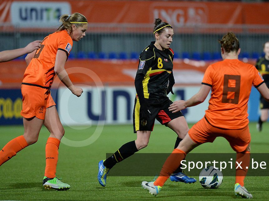 20140212 - ZWOLLE , THE NETHERLANDS : Belgian Audrey Demoustier (8) pictured surrounded by Dutch Anouk Dekker (l) during the female soccer match between The Netherlands and Belgium , on the fifth matchday in group 5 of the UEFA qualifying round to the FIFA Women World Cup in Canada 2015 at Het Ijseldelta Stadion , Zwolle . Wednesday 12th February 2014 . PHOTO DAVID CATRY