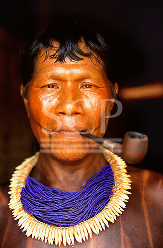 A-Ukre village, Xingu, Brazil. Poti, a Kayapo man, smoking a commercially made pipe, wearing blue beads and tooth necklace