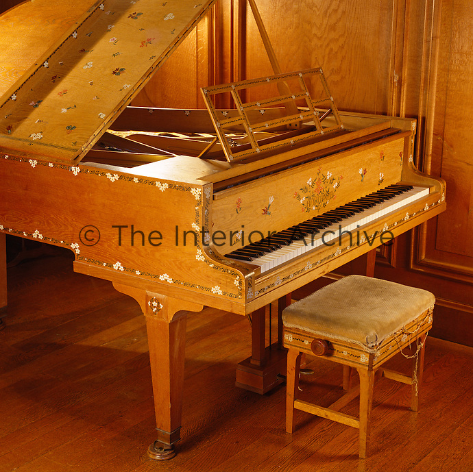 This wooden grand piano is covered in delicate hand-painted floral motifs