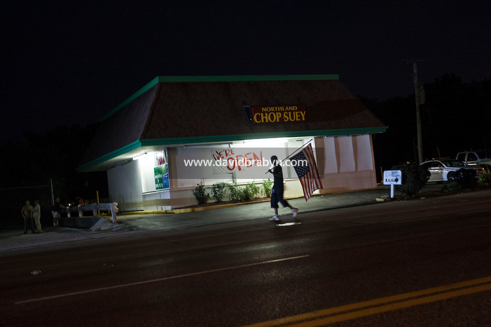 HSUL 20140818 United States, Ferguson, MO. A protestors walks past a bordered up restaurant on West Florissant Avenue in Ferguson, Missouri, on August 18, 2014. Photographer: David Brabyn
