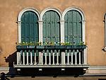 Three shuttered doors and balcony and flowers, along Fondamenta dei Vetrai on the main canal of Murano, Italy