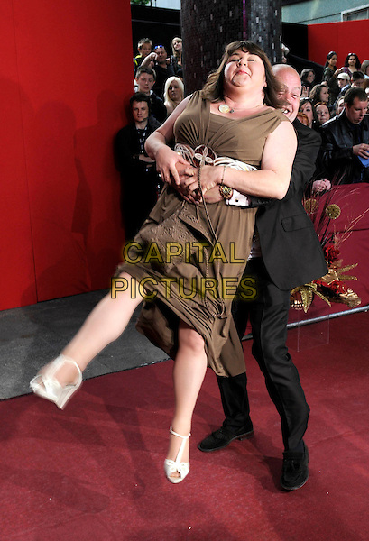 CHERYL FERGISON & CLIFF PARISI.Arrivals - the British Soap Awards 2009, BBC Television Centre, Wood Lane, London, England..May 9th 2009.soaps tv full length Eastenders green brown khaki dress long maxi suit arms around waist hug embrace funny lifting carrying picking up ferguson.CAP/FIN.©Steve Finn/Capital Pictures.