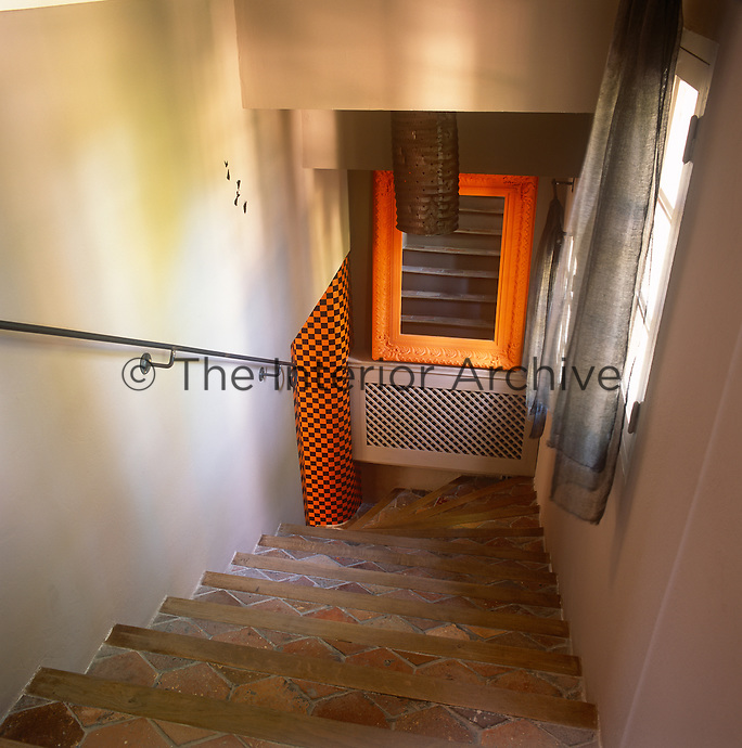 A view down a stone staircase with terracotta tiled treads.