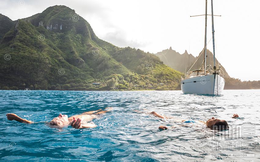 A couple enjoy the warm waters off their anchored sailboat on the Na Pali Coast of Kaua'i.
