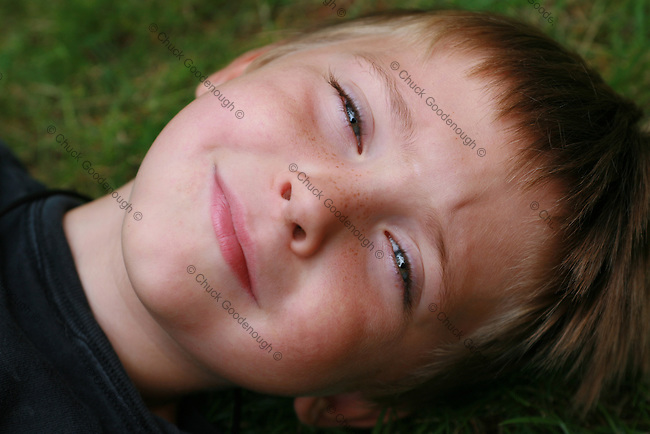 Smiling & Relaxing in the Grass, a Small Boy is Grinning at Camera