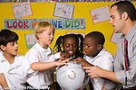 Elementary school classroom children with special needs, male teacher looking at globe with small group of students