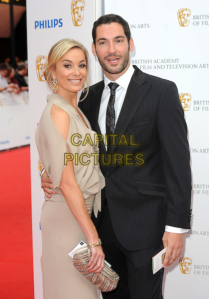 TAMZIN OUTHWAITE & TOM ELLIS.at the Philips British Academy Television Awards (BAFTA) at the London Palladium, London, England,.June 6th, 2010..BAFTAs TV half length arrivals black suit tie husband wife couple married brown nude beige catsuit clutch bag gold jumpsuit cut out shoulder pinstripe .CAP/BEL.©Tom Belcher/Capital Pictures.