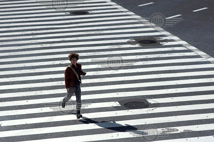 A young man crosses a road in Shibuya using a pedestrian crossing (Zebra Crossing). /Felix Features