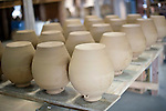 Earthenware flasks for use in specially brewed awamori are dried prior to firing in kilns at the Chuko distillery in Naha, Okinawa Prefecture, Japan, on May 20, 2012. Photographer: Robert Gilhooly