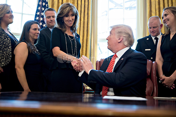 United States President Donald Trump, right, shakes hands with Tammie Jo Shults, a Southwest Airlines Co. captain, while meeting with the crew and passengers of Southwest Airlines flight 1380 in the Oval Office of the White House in Washington, D.C., U.S., on Tuesday, May 1, 2018. An engine on Southwest's flight 1380, a Boeing Co. 737-700 bound for Dallas from New York's LaGuardia airport, exploded and made an emergency landing on April 17 sending shrapnel into the plane and killing a passenger seated near a window. <br /> Credit: Andrew Harrer / Pool via CNP /MediaPunch