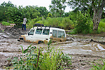 The Toyota LandCruiser of the international social marketing organization, Population Services International (PSI), braves the muddy water on the road between Rumbek and Mundri, South Sudan.  After decades of civil war, South Sudan boasts only a few kilometers of paved road.  At the time of this photo, the 150-mile journey from Rumbek to Mundri took up to two days to travel.