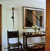 A horn lamp and framed textile on the wall of the staircase hall