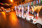 Amador Flower Farm with Jeanne and Ken Deaver driving their tram in Sutter Creek's annual Parade of Lights Christmas parade downtown on a rainy night in the  Mother Lode of Calif.