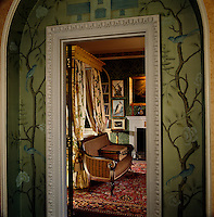 Chinoiserie wallpaper frames the doorway leading to the bedroom