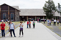 People stand outside the Old Faithful Lodge (rear) to watch as Old Faithful erupts in Yellowstone National Park, Wyoming, USA. In the days surrounding when this image was taken, the geyser averaged an eruption about every 90 minutes, though occasionally there were hours between eruptions.