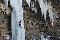 An Ice Climber ascends a steep, frozen waterfall near Vail, Colorado.