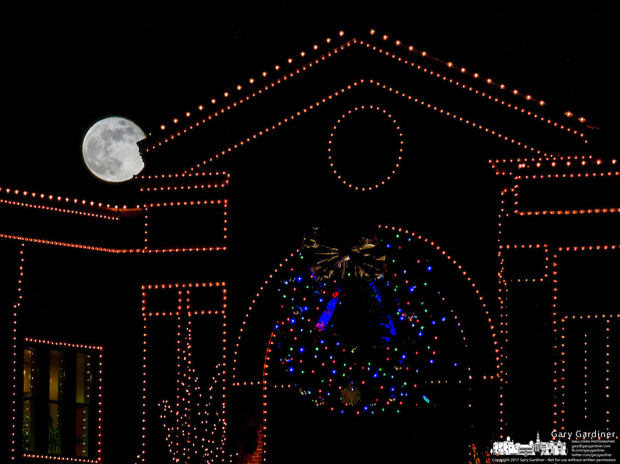 Full moon rises over a storefront decorated with Christmas lights..