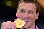 LONDON, ENGLAND - JULY 28:  Ryan Lochte of the USA bites the gold medal from the Men's 400M Individual Medley Final with an American Flag diamond studs mouthpiece during Day 2 of the Swimming Finals as part of the London 2012 Olympic Games on July 28, 2012 at the Aquatics Center in London, England. (Photo by Donald Miralle)