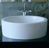 A circular wash basin against a granite splashback