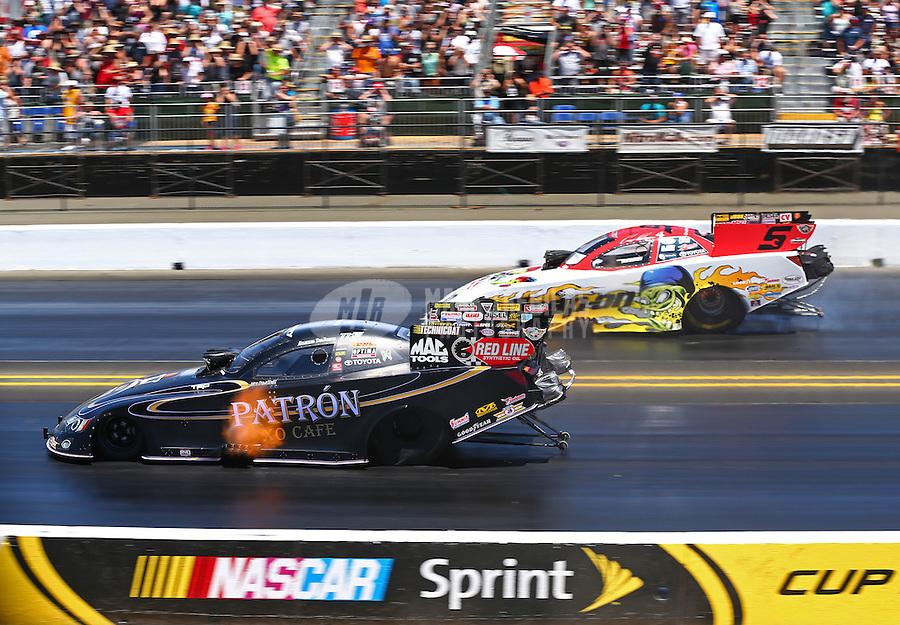Jul. 27, 2014; Sonoma, CA, USA; NHRA funny car driver Alexis DeJoria (near) races alongside Cruz Pedregon during the Sonoma Nationals at Sonoma Raceway. Mandatory Credit: Mark J. Rebilas-