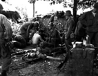Wounded American soldiers are given medical treatment at a first aid station, somewhere in Korea.  July 25, 1950.  Pfc. Tom Nebbia. (Army)<br /> NARA FILE #:  111-SC-344399<br /> WAR & CONFLICT BOOK #:  1450