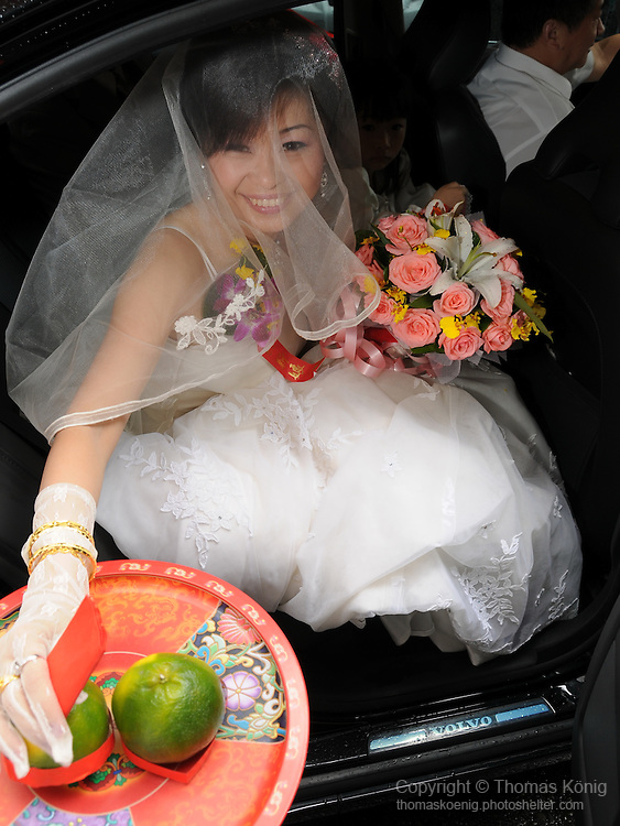 Taiwanese Wedding -- Arrival at the groom's hotel.<br /> <br /> The couple is received with offerings of two oranges.<br /> In Mandarin Chinese, the word for orange ('ju') sounds very similar to 'ji', a character meaning 'lucky', 'auspicious' or 'favorable'.<br /> Oranges are thus considered to bring the couple good luck.