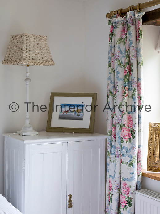 A white-painted cupboard is used as a bedside table in this fresh and pretty bedroom