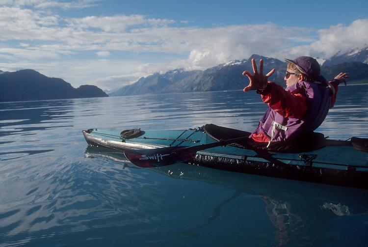 Alaska, Glacier Bay National Park, Woman kayaker celebrating, stretching in sunshine, Alaska's John Hopkins Inlet..
