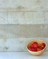 Detail of a contemporary wooden fruit bowl full of apples against a concrete wall