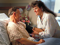 Nurse taking blood pressure of male patient in hospital. United States Hospital.