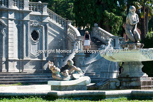 Public park with a stone fountain and a curved staircase in Tremezzo, a town on Lake Como, Italy