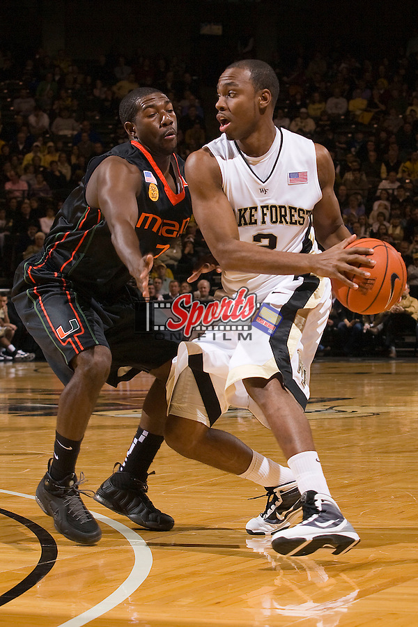 Gary Clark #2 of the Wake Forest Demon Deacons looks to make a pass while being defended by Malcolm Grant #3 of the Miami Hurricanes at the Lawrence Joel Veterans Memorial Coliseum February 2n Winston-Salem, NC.  The Demon Deacons defeated the Hurricanes 64-57.  Brian Westerholt / Sports On Film