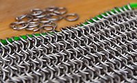 A sheet of European 6 in 1 chain mail in the front, with rings ready to be attached in the background.