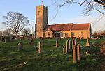 Late afternoon winter golden light falls on Saint John the Baptist church, Snape, Suffolk, England, UK