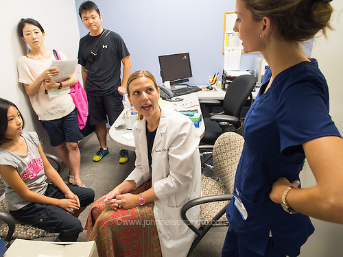 Physician Assistant Leocadia Conlon instructs student PA Lauren Holland while examining Marin Yoshida at the School Physicals event at South County Government Center in Alexandria, Virginia on Aug. 11, 2013.