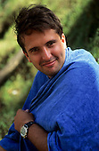 Sao Paulo State, Brazil. Smiling man wrapped in a blue towel wearing a wristwatch.