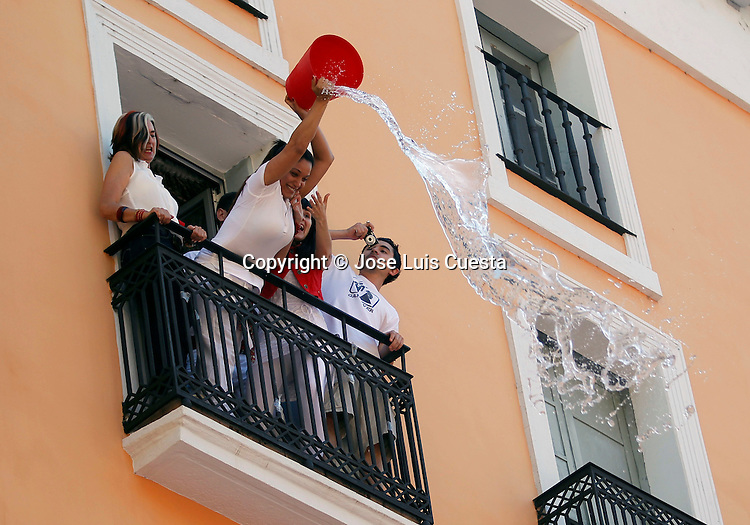 "Some people throwing water over revelers which are enjoying of the first day of Sanfermines in city hall square, in Pamplona, northern of Spain. San Fermin starts with the launch of a rocket, which is known as ""chupinazo"". San Fermin festival is worldwide known because the daily running bulls."