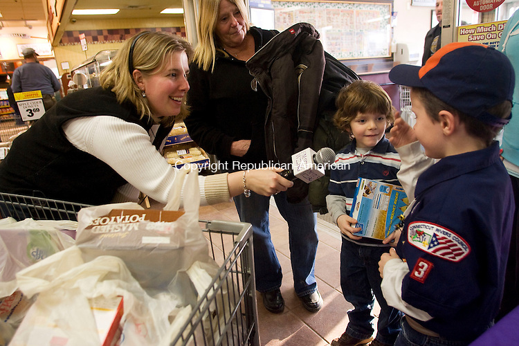 TORRINGTON, CT - 06 MARCH 2009 -030609JT02-<br /> WZBG radio station DJ Amy Ferrarotti interviews Jacob Regner, 6, right, and his brother Evan, 5, as their grandmother Ann Regner looks on after they donated items to the United Way of Northwest Connecticut's Food for Your Neighbors drive at Price Chopper in Torrington on Friday afternoon. <br /> Josalee Thrift Republican-American