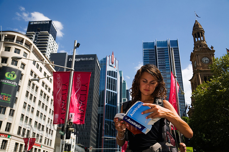 A backpacker checks her guidebook for directions in the city.  Sydney, New South Wales, AUSTRALIA.