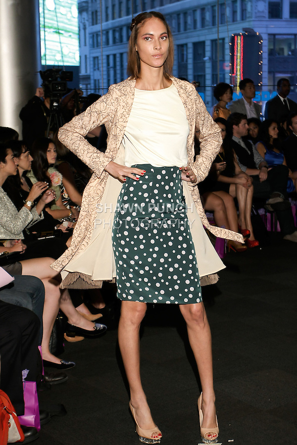 """Model walks runway in a lace trench coat with cream t-shirt and green polka dot skirt, from the Yuna Yang Spring Summer 2013 """"Close your eyes and see the world"""" collection, at the NASDAQ Marketsite, during New York Fashion Week, on September 7, 2012."""