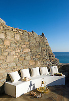 A gently curved stone wall serves as a backrest to this simple concrete bench which is positioned to take advantage of the evening sunshine