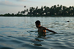 A young man takes a dip, at the foot of the Athawkarma Magyi Monastery as the sun sets, and the moon rises! The monastery lies at the mouth of a river in the Ayeyarwaddy Delta.