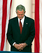 Washington, D.C. - May 29, 2006 -- United States President George W. Bush bows his head in prayer prior to making remarks at the annual Arlington National Cemetery Memorial Day Commemoration at Arlington National Cemetery in Arlington, Virginia  on May 29, 2006. <br /> Credit: Ron Sachs  - Pool via CNP