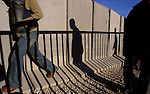 Palestinians walk pass the security wall which separates between the Palestinian neighbor of Abu Dis and Jerusalem.