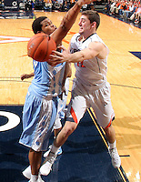 Virginia guard Joe Harris (12) passes the ball around North Carolina forward Kennedy Meeks (3) during an NCAA basketball game against Virginia Monday Jan. 20, 2014 in Charlottesville, VA. Virginia defeated North Carolina 76-61.