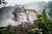 A government bulldozer demolishing a farm house during a forced removal on the outskirts of a Chinese city.<br /> <br /> The house had been marked by the government to make way for urban development. <br /> <br /> (The image is shot for Justin Jin by an anonymous person with special access to the situation. Justin Jin visited the location with the person ahead of the demolition to discuss the shoot as evidence of involuntary demolition).