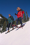 A couple snowshoeing downhill in the Rocky Mountains of Colorado near Estes Park, USA