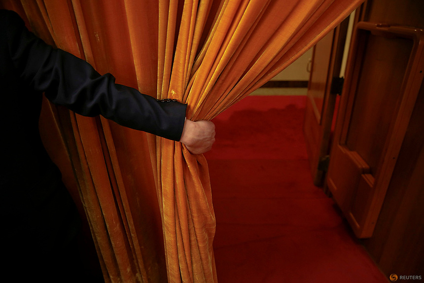 A security agent opens a curtain covering the entrance of a main hall inside the Great Hall of the People where sessions of the National People's Congress (NPC) and the Chinese People's Political Consultative Conference (CPPCC) are taking place, in Beijing, China March 5, 2016.   REUTERS/Damir Sagolj