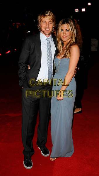 "OWEN WILSON & JENNIFER ANISTON.""Marley & Me"" UK film premiere held at Vue cinema, Leicester Square, London, England..March 2nd, 2009. .full length blue long maxi dress strapless gold necklaces chains Burberry silk down beige black trainers grey gray suit tie floor-length georgette hand in pocket .CAP/CAN.©Can Nguyen/Capital Pictures."