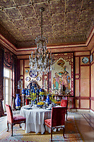 The opulent 19th century apartment  exudes sensuality, fantasy and passion. Sculpted coffered ceilings and wood walls in the dining room are the perfect backdrop for the collections of 18th century antique Chinese vases and Japanese Imari plates (Meiji period), as well as the monumental French Chinoiserie style painting.